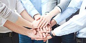 Team: Hände übereinander gelegt