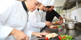 Köche richten etwas in einer Großküche an
